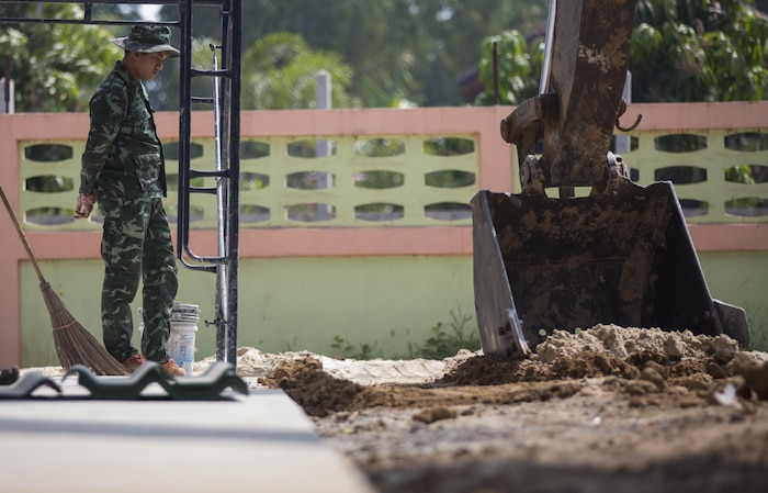 A Royal Thai Air Force airman watches an excavator dig at Ban Non Lueam School, Korat Province, Thailand during exercise Cobra Gold, Feb. 13, 2017.  Cobra Gold 17 maintains a consistent focus on humanitarian civic action, community engagement, and medical activities conducted during the exercise to support the needs and humanitarian interests of civilian populations around the region. (U.S. Marine Corps Combat Camera photo by Staff Sgt. Nathan O. Sotelo)