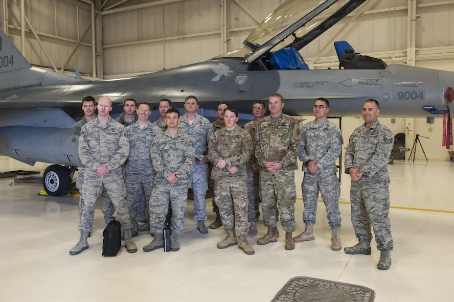 Explosive Ordnance Disposal team members, assigned to the 734th Explosive Ordnance Company EOD at Fort Bliss, Texas and the 49th Civil Engineer Squadron EOD flight pose for a picture at Holloman Air Force Base, N.M. Feb. 14, 2017. The two teams participated in joint training in which the 49th EOD team taught the 734th EOD team pinning procedures on an F-16 Fighting Falcon. (U.S. Air Force photo by Airman Ilyana A. Escalona)