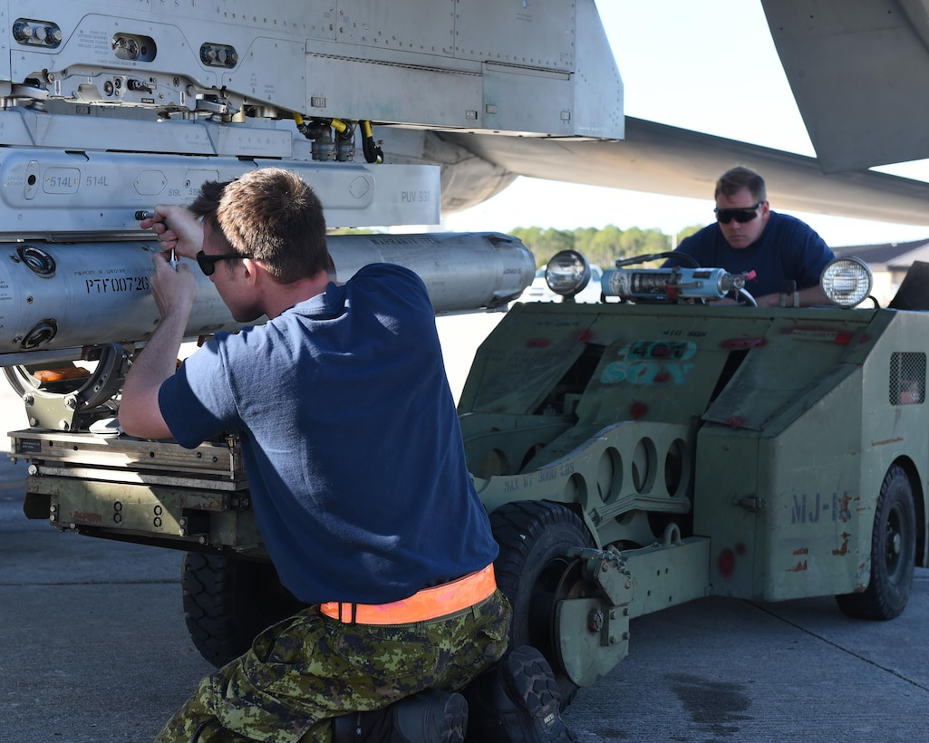 Royal Canadian Air Force weapons systems specialists from the 401st Tactical Fighter Squadron attach a training weapon to a CF-18 Hornet at Tyndall Air Force Base, Fla., Jan. 31, 2017. The Combat Archer and Combat Hammer exercises marked the first time that the 401st TFS deployed a detachment of personnel since fall 2015. (U.S. Air Force photo by Airman 1st Class Cody R. Miller/Released)