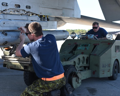 Royal Canadian Air Force weapons systems specialists from the 401st Tactical Fighter Squadron attach a training