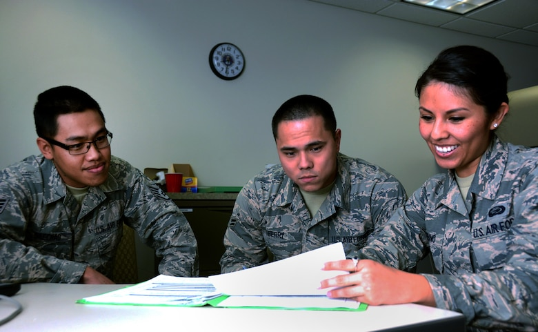 Staff Sgt. Saecho Kao Seng, 349th Force Support Squadron personnel specialist, aids Airmen 1st Class Justin Ferry and Samantha Bambino, 60th Force Support Squadron personnel specialists, in commissioning packages for Airmen assigned to the 349th Air Mobility Wing at Travis Air Force Base, Calif., on Feb. 15, 2017. The 60th and 349th FSS units have been working together to become a seemless unit and Total Force Support Squadron in March. (U.S. Air Force photo/Staff Sgt. Daniel Phelps)