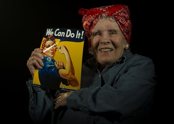 "Margaret ""Peggy"" Wills, B-24 electrician during World War II, holds a recruitment poster at Minot Air Force Base, Feb. 9, 2017. Wills was a Rosie the Riveter at Holman Field in St. Paul, Minn. (U.S. Air Force photo/Senior Airman Apryl Hall)"