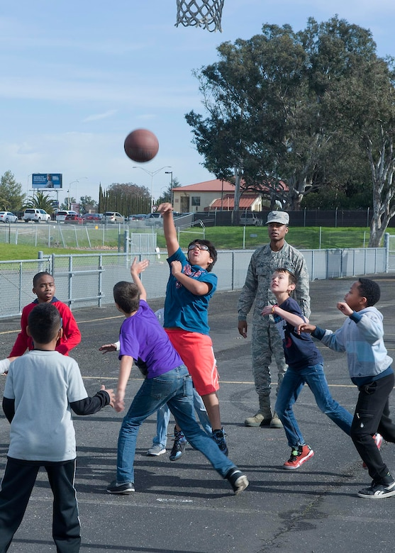 Airman 1st Class Adam Taylor, 60th Contracting Squadron, supervises children playing a basketball game at Travis Elementary School at Travis Air Force Base, Calif., Feb. 7, 2017. Taylor is a regular volunteer at the school as a yard monitor. (U.S. Air Force  photo/T.C. Perkins Jr.)