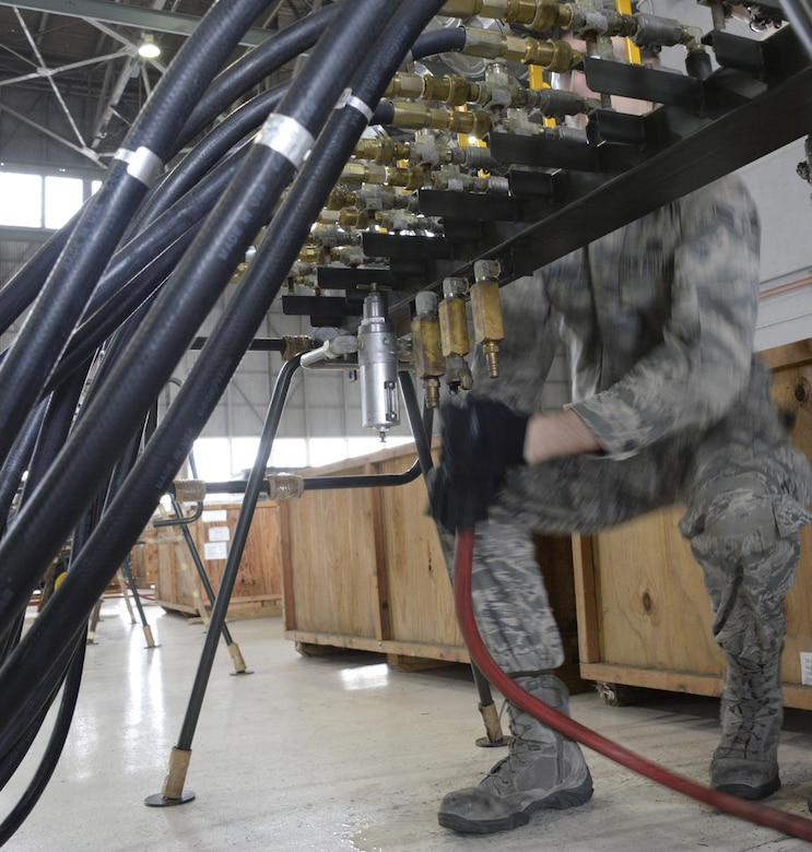 An Airman from the 60th Maintenance Squadron disconnects a hydraulic hose during the annual quality assurance inspection of the crash, damaged or disabled aircraft recovery program Feb. 9, 2017 at Travis Air Force Base, Calif. The lifting bags, capable of supporting up to 52,000 pounds individually, are used to lift a downed aircraft so it can be salvaged, repaired and recovered.  (U.S. Air Force photo by Senior Airman Amber Carter)