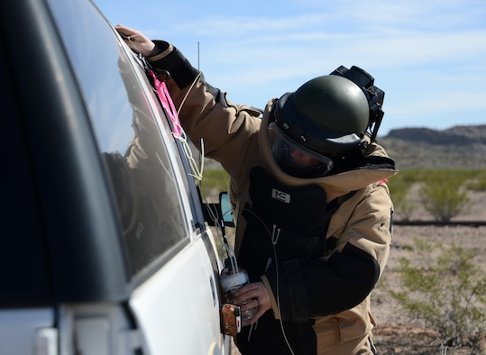 Staff Sgt. Timothy Doland, 56th Civil Engineer Squadron explosive ordnance disposal team leader, places a water bottle charge on the side of a vehicle during a contingency problem Feb. 8, 2017, at the Barry M. Goldwater Range in Gila Bend, Az. Throughout the exercise, EOD Airmen were challenged with various contingency problems in which they had to detect, defuse, and destroy potential roadside bomb threats. (U.S. Air Force photo by Airman 1st Class Alexander Cook)