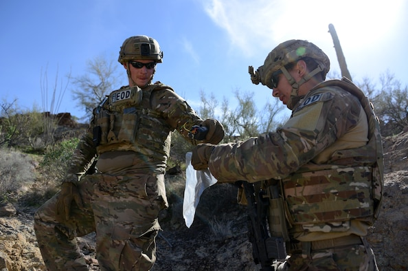 Staff Sgt. Timothy Doland, 56th Civil Engineer Squadron explosive ordnance disposal team lead, and Airman 1st Class Tahir Finley, 56th CES EOD team member, collect evidence during a contingency problem Feb. 8, 2017, at the Barry M. Goldwater Range in Gila Bend, Az. EOD Airmen collect evidence for intelligence purposes. (U.S. Air Force photo by Airman 1st Class Alexander Cook)