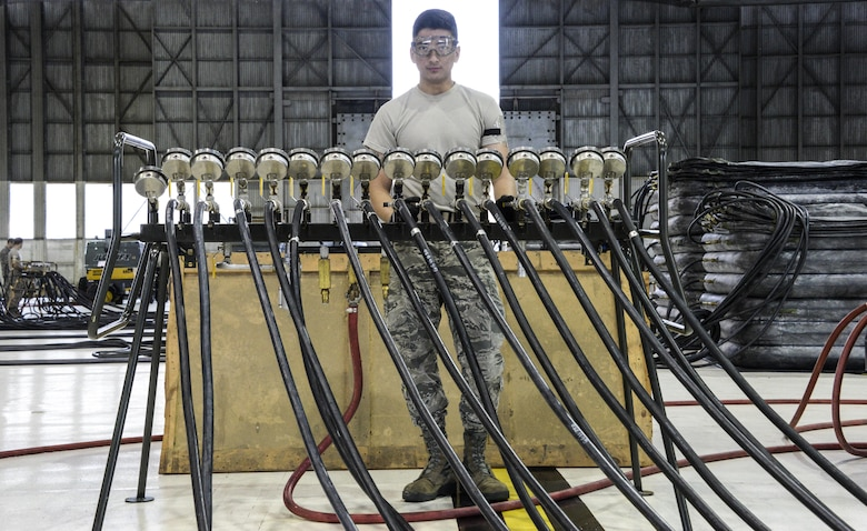 An Airman from the 60th Maintenance Squadron monitors the pounds per square inch while inflating lifting bags during an annual quality assurance inspection of the crash, damaged or disabled aircraft recovery program Feb. 9, 2017 at Travis Air Force Base, Calif. The lifting bags, filled to 7 PSI during the inspection, are used to lift a downed aircraft so it can be salvaged, repaired and recovered.  (U.S. Air Force photo by Senior Airman Amber Carter)