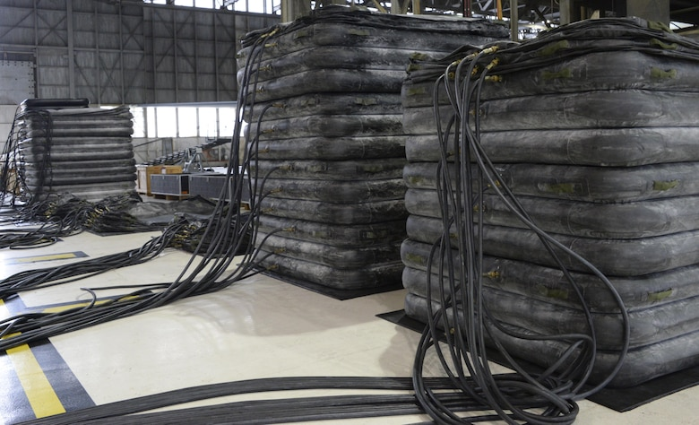 Airmen from the 60th Maintenance Squadron inspect large lifting bags for leaks during an annual quality assurance inspection of the crash, damaged or disabled aircraft recovery program Feb. 9, 2017 at Travis Air Force Base, Calif. The lifting bags, capable of supporting up to 52,000 pounds individually, are used to lift a downed aircraft so it can be salvaged, repaired and recovered.  (U.S. Air Force photo by Senior Airman Amber Carter)