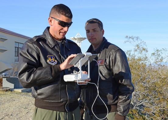 Maj. William Niblack, Emerging Technologies Combined Test Force, operations officer (left), pilots a quadcopter on the second test sortie Feb. 13. Maj. Danny Riley, ET CTF director (right) piloted the third and final sortie. The test was conducted to see if it's possible to use a small unmanned aerial system to calibrate Edwards AFB's telemetry antennas. (U.S. Air Force photo by Kenji Thuloweit)