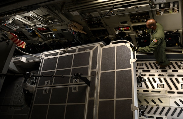 U.S. Air Force Senior Airman Andre Phillip, 732nd Airlift Squadron loadmaster, assigned to Joint Base McGuire-Dix-Lakehurst, N.J., signals the movement of a security boat on to a C-17 Globemaster III at Joint Base Langley-Eustis, Va., Feb. 8, 2017. Airmen from both Air Force bases and U.S. Coast Guardsmen worked together to load boats and a large equipment pallet on to the aircraft. (U.S. Air Force photo by U.S. Airman 1st Class Kaylee Dubois)