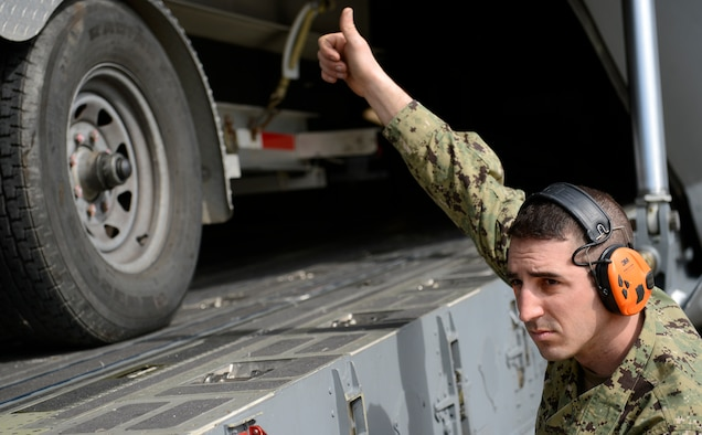 U.S. Coast Guard Machinery Technician 1st Class Eric Zupan, Port Security Unit 305 crewmember, signals a to forklift operator while loading security boats onto a C-17 Globemaster III at Joint Base Langley-Eustis, Va., Feb. 8, 2017. Zupan and his team loaded their equipment onto the aircraft in preparation for a joint task force deployment. (U.S. Air Force photo by U.S. Airman 1st Class Kaylee Dubois)