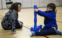 Pandora Howell, 733rd Civil Engineer Division portfolio optimization chief, provides guidance as Ralph Belford, VI, age eight, son of U.S. Army Sgt. 1st Class Ralph Belford, V, Army Training Support Center NCO, builds a tower during the Family science, technology, engineering and mathematics Night event at Gen. Stanford Elementary School at Joint Base Langley-Eustis, Va., Feb. 9, 2017. Architectural and design professionals attended the event to help students understand how math, height and stability work together when building tall towers. (U.S. Air Force photo by Staff Sgt. Teresa J. Cleveland)