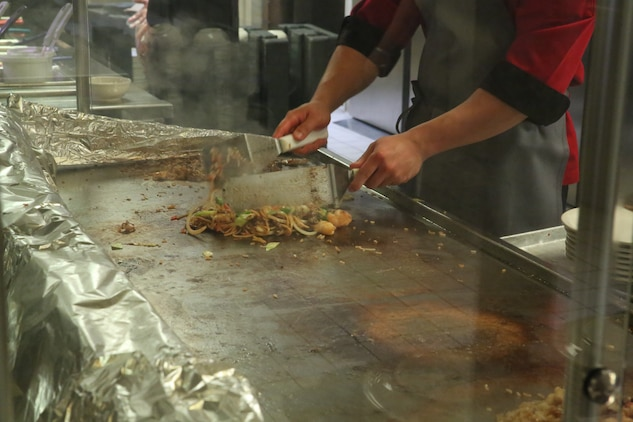 A food service specialist cooks Mongolian entrée selections on the grill during Mongolian Bar Wednesday in the R.G. Robinson Mess Hall at Marine Corps Air Station Iwakuni, Japan, Feb. 8, 2017. Mongolian Bar Wednesday was started in an effort to attract more patrons to the mess halls by offering specialty meals such as the Mongolian Bowl. (U.S. Marine Corps photo by Lance Cpl. Carlos Jimenez.)