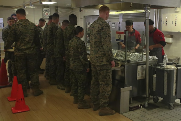 U.S. Marines wait in line while food service specialists sauté Mongolian entrée selections on the grill during Mongolian Bar Wednesday in the R.G. Robinson Mess Hall at Marine Corps Air Station Iwakuni, Japan, Feb. 8, 2017. Mongolian Bar Wednesday was started in an effort to attract more patrons to the mess halls by offering specialty meals such as the Mongolian Bowl. (U.S. Marine Corps photo by Lance Cpl. Carlos Jimenez.)