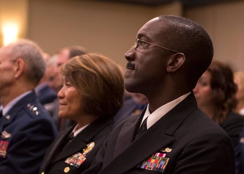 "Navy Capt. James Ellzy, Defense Health Management Systems executive officer, watches a guest speaker during a ""go-live"" recognition ceremony for MHS Genesis Feb. 15, 2017, at Fairchild Air Force Base, Wash. Ellzy was the master of ceremonies during the event. (U.S. Air Force photo/Airman 1st Class Ryan Lackey)"
