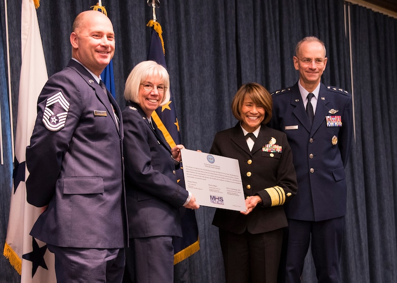 "(From left to right) Chief Master Sgt. Willard Armagost, 92nd Medical Group superintendent, Col. Meg Carey, 92nd MDG commander, Navy Vice Admiral Raquel Bono, Defense Health Agency director, and Lt. Gen. Mark Ediger, U.S. Air Force surgeon general, pose with a plaque in honor of the MHS Genesis ""go-live"" Feb. 15, 2017, at Fairchild Air Force Base, Wash. MHS Genesis is a Department of Defense wide initiative to move to an all digital, networked medical record system. (U.S. Air Force photo/Airman 1st Class Ryan Lackey)"