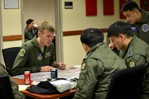 U.S. Air Force Capt. James Rosenau, 25th Fighter Squadron pilot, discusses a flight plan with Republic of Korea air force personnel during Buddy Wing 17-3 at Osan Air Base, ROK, Feb. 14, 2017. Buddy Wing exercises are held throughout the year at different air bases across the ROK, bringing together different elements of U.S. and ROK air force assets for bi-lateral training and the exchange of skills. (U.S. Air Force photo by Staff Sgt. Victor J. Caputo)