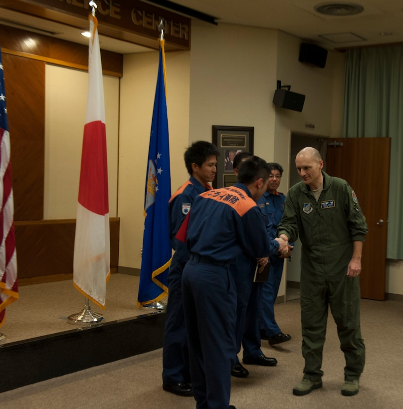 U.S. Air Force Col. John Cotton, 18th Aerospace Medicine Squadron commander, shakes hands with Nirai Fire Department members Feb. 13, 2017, at Kadena Air Base, Japan. Cotton and the Nirai Fire Department members worked together to save the life of a local woman Feb. 3 when she was struck by a car while riding her bicycle. (U.S. Air Force photo by Senior Airman Lynette M. Rolen/Released)