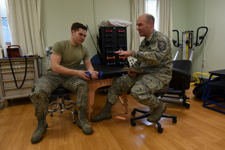 U.S. Air Force Master Sgt. Gregory Dorner, 8th Medical Operations Squadron Physical Therapy flight chief, talks with Senior Airman Tyler Macmillan, 8th Logistics Readiness Squadron Material Handling Equipment maintenance journeyman, about his treatment progress while performing wrist exercises during a physical therapy appointment at Kunsan Air Base, Republic of Korea, Feb. 13, 2017. The physical therapy section is responsible for ensuring proper healing and rehabilitation of Airmen who have injuries or are recovering from surgeries. Once approved through their primary care manager, Airmen can make an appointment to visit the physical therapy section to ensure they are in the best shape to perform their duties. (U.S. Air Force photo by Senior Airman Michael Hunsaker/Released)