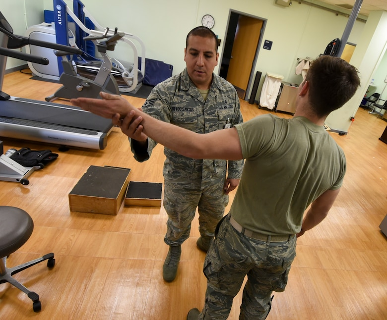 U.S. Air Force Staff Sgt. Pedro De Los Santos, 8th Medical Operations Squadron Physical Therapy noncommissioned officer in charge, assists Senior Airman Tyler Macmillan, 8th Logistics Readiness Squadron Material Handling Equipment maintenance journeyman, with elbow mobilization and nerve glide exercises during a physical therapy appointment at Kunsan Air Base, Republic of Korea, Feb. 13, 2017. De Los Santos ensures proper movement and function through rehabilitation of Macmillan's arm, which was injured while lifting weights at the gym. (U.S. Air Force photo by Senior Airman Michael Hunsaker/Released)
