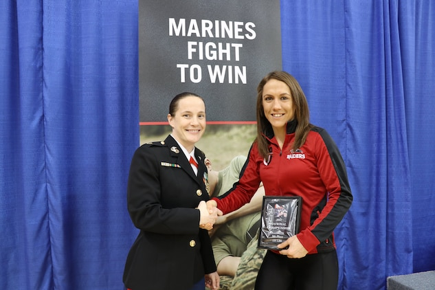 Former wrestler, Maj. Jill McQuistan, presents an award to Marine veteran, Kalyn Schwartz, Feb. 10-11, at the Women's Collegiate Wrestling Association National Championships in Oklahoma City. Marine Corps Recruiting Command's marketing relationship with USA Wrestling is focused on locating and recruiting physically and mentally well-equipped young men and women who share the same values of honor, courage and commitment. (U.S. Marine Corps photo by Cpl. Jennifer Webster/Released)