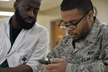 Willie Hayes, occupational therapist, Walter Reed National Military Medical Center, Bethesda, Maryland, works with Staff Sgt. Rasheed, 7th Intelligence Squadron, on a memory exercise where he reads excerpts from the internet, writes what he remembers, then gives a short synopsis without his notes during occupational therapy Jan. 17. Rasheed suffered a cerebral aneurysm in 2015. Part of his recovery is working on occupational exercises. (U.S. Air Force photo/Staff Sgt. Alexandre Montes)