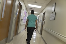 Staff Sgt. Rasheed, 7th Intelligence Squadron, walks the hallways of Walter Reed National Military Medical Center in Bethesda, Maryland, to his occupational therapy appointment Jan. 17. Rasheed suffered a cerebral aneurysm in 2015 and part of his recovery to return to service is working on occupational exercises. (U.S. Air Force photo/Staff Sgt. Alexandre Montes)