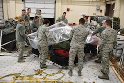 Members of the 120th Airlift Wing Medical Group and Small Air Terminal wrap a baggage pallet in preparation for loading on a C-130 Hercules aircraft at Great Falls International Airport Sunday. Guardsmen will be attending medical readiness training in Anniston, Ala. (U.S. Air National Guard photo by Master Sgt. Michael Touchette)