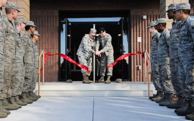 Col. Paul Murray, 99th Air Base Wing commander, and Airman 1st Class Nicholas Martini, 99th Security Forces Squadron, cut the ceremonial ribbon for the new dormitory during a ceremony on Nellis Air Force Base, Nev., Feb. 3, 2017. The new facility's amenities include ample parking spaces, basketball court, sand volleyball court, and multiple shaded outdoor seating areas. (U.S. Air Force photo by Airman 1st Class Kevin Tanenbaum/Released)