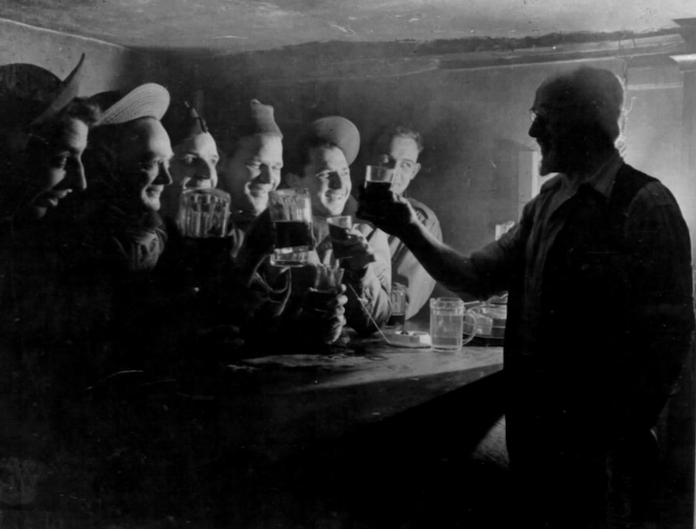 "Publican ""Pop"" Potter raises a glass to Airmen of the 55th Fighter Group inside of the Woodman Inn pub located at Nuthampstead, England, during the World War II. The pub was located within the United States Army Air Force's post 131 border and was visited by American Airmen during their brief stay at Nuthampstead. (Ucourtesy photo from Russ Abbey)"