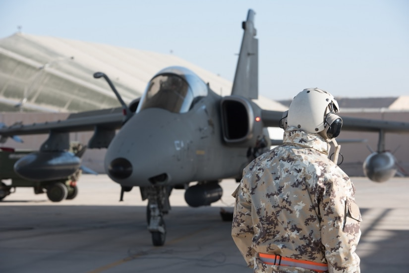 """An Italian air force maintainer watches while Air Force Lt. Col. Joe """"Slap"""" Goldsworthy, a pilot assigned to the Italian air force 132nd Groupo as part of the Military Personnel Exchange Program, prepares to taxi in an AMX A-11 Ghibli aircraft at an undisclosed location in Southwest Asia, Jan. 11, 2017. Goldsworthy has served with the Italian air force for nearly three years as a fully integrated member of the 132nd Groupo. Air Force photo by Master Sgt. Benjamin Wilson"""