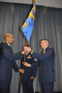 Commander of the 960th Cyberspace Operations Group, Col. Anthony Perkins, left, passes the 689th guidon to Maj. Kevin Deibler, new commander of the 689th Networks Operations Squadron, during an Assumption of Command ceremony Feb. 12, at Gunter Annex. The 689th is the Air Force's newest Net Ops Squadron in the Cyber fight. (U.S. Air Force photo by Bradley J. Clark)
