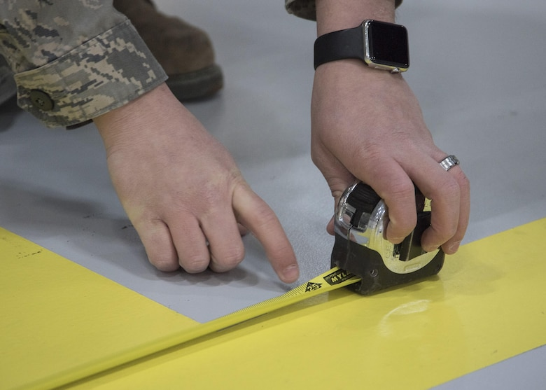 Senior Airman Ivan Abrev, 11th Civil Engineer Squadron structural journeyman, uses a measuring tape at Joint Base Andrews, Md., Feb. 16, 2017. Abrev measured several distances within a hangar to determine where to place an F-16 Fighting Falcon display and U.S. flags in preparation for the Chief Master Sergeant of the Air Force Transition Ceremony. (U.S. Air Force photo by Senior Airmen Jordyn Fetter)