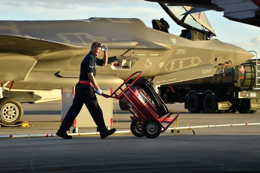 Airman 1st Class Nathan Kosters, a crew chief with the 34th Aircraft Maintenance Unit, Hill Air Force Base, Utah, moves a halon bottle while fueling an F-35A Lightning II aircraft Feb. 7 during Red Flag 17-1 at Nellis Air Force Base, Nevada. (U.S. Air Force photo by R. Nial Bradshaw)