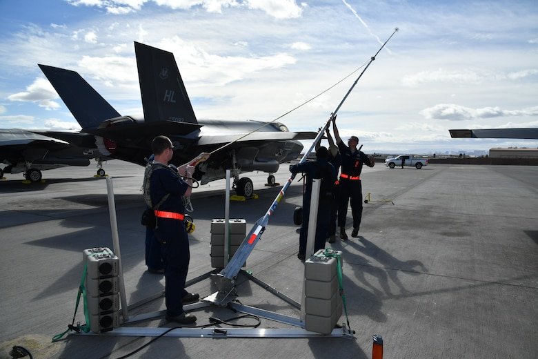 Crew chiefs from Hill Air Force Base, Utah, lower a lightning protection rod Feb. 7 at Nellis Air Force Base, Nevada, during Red Flag 17-1. (U.S. Air Force photo by R. Nial Bradshaw)