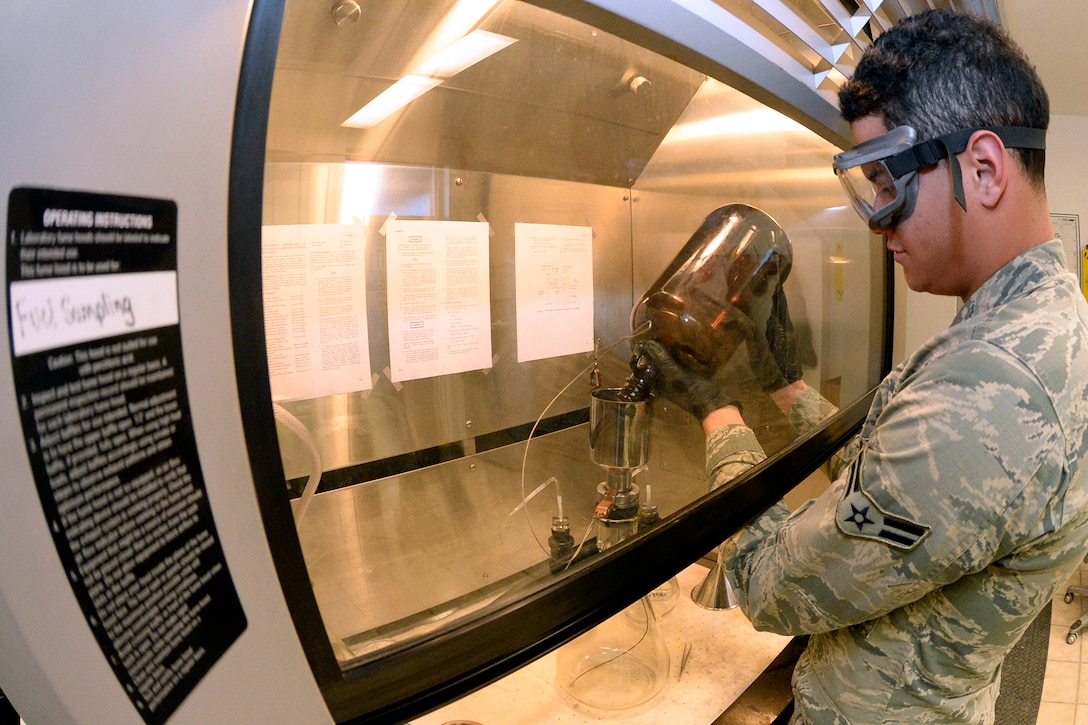 Airman 1st Class Anthony Louden, 75th Logistics Readiness Squadron fuels lab technician, tests for particulates in aviation fuel using the bottle method, Feb. 14, 2017, at Hill Air Force Base, Utah. Before use by the base, all fuels are tested by 75th LRS technicians, who pour fuel samples through test pads and then weigh the particulates trapped on pads to determine if the fuel is within the acceptable parameters. (U.S. Air Force photo by Todd Cromar)