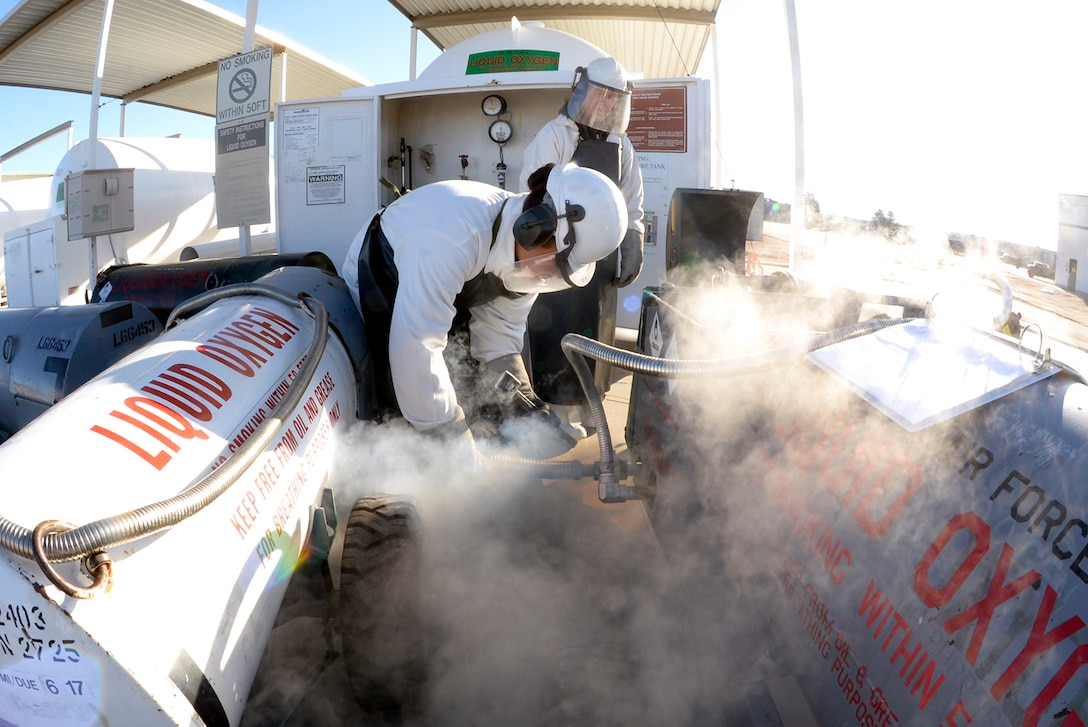 Senior Airmen Ginnethon Pauula, front, and David Day, both 75th Logistics Readiness Squadron facilities operators, fill 50-gallon oxygen carts with liquid oxygen Feb. 14, 2017, at Hill Air Force Base, Utah. After filling, the oxygen are sampled before being turned over to aircraft maintenance crews who replenish aircraft with oxygen to be used during flight. (U.S. Air Force photo by Todd Cromar)
