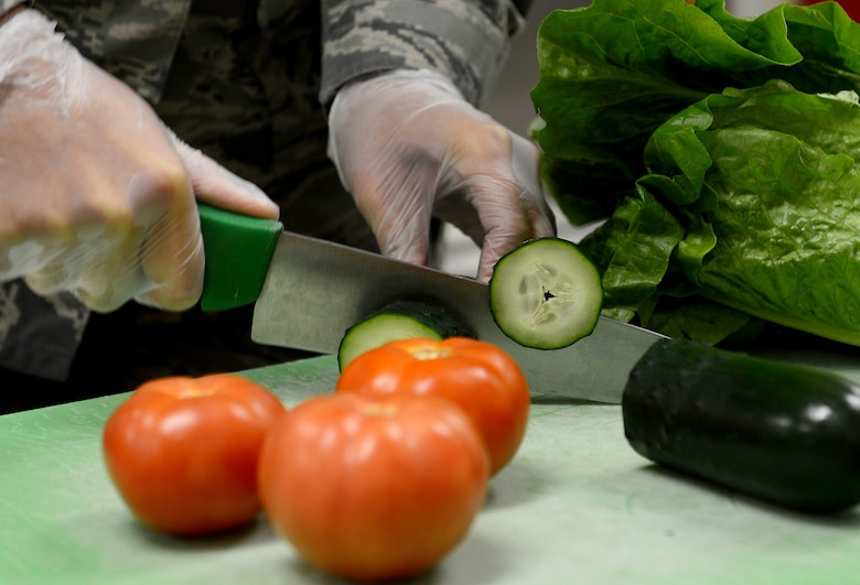 Airman 1st Class Arlena Harges, 627th Force Support Squadron food services apprentice, cuts vegetables for sandwiches and salads in the McChord flight kitchen Feb. 14, 2017 at Joint Base Lewis-McChord, Wash. The entrées for the boxed meals includes different types of sandwiches including turkey, ham and roast beef. They also have breaded chicken strips and a chef salad, as well as breakfast items. The supplemental options are often pre-contained food items such as chips, cookies, fresh fruit and your choice of beverage. (U.S. Air Force photo/Senior Airman Divine Cox)
