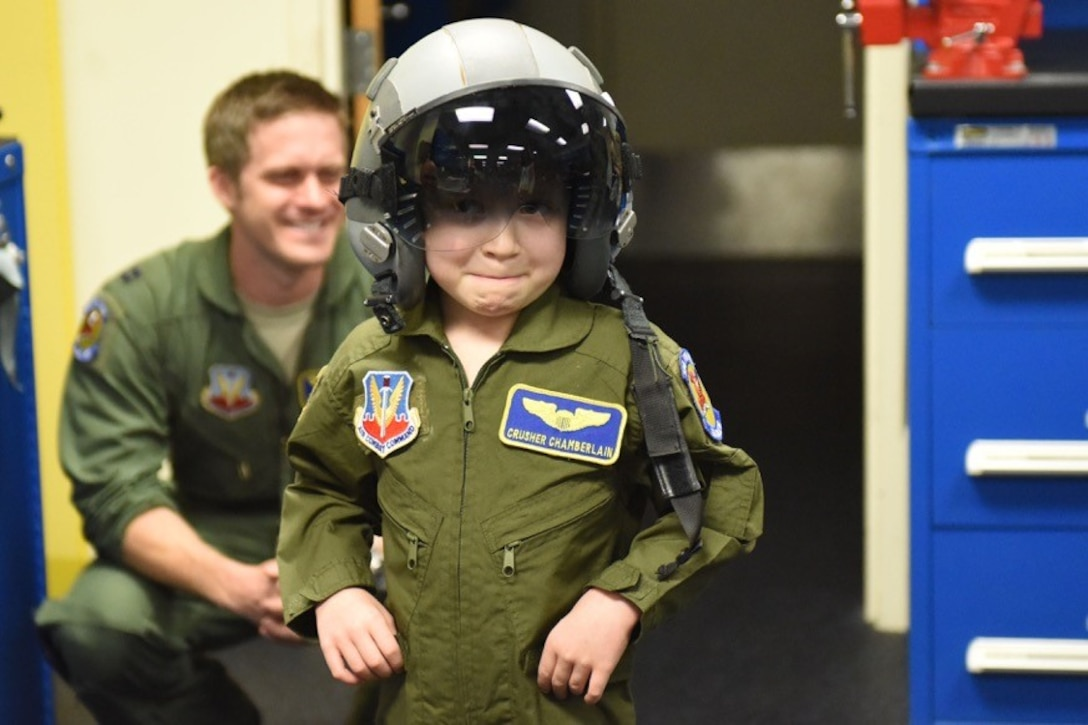 "Alexis ""Crusher"" Chamberlain tries on her helmet and flight suit during a Pilot for a Day program event, Feb. 15, 2017, at Seymour Johnson Air Force Base, North Carolina. This event provides children with serious or chronic medical conditions, and their families with the opportunity to be a guest of the 4th Fighter Wing. (U.S. Air Force photo by Airman Miranda A. Loera)"