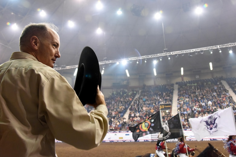 U.S. Air Force Col. Michael Downs, 17th Training Wing Commander, stands for passing of the colors during the 85th Annual San Angelo Stock Show and Rodeo Military Appreciation Night at the Foster Communications Coliseum in San Angelo, Texas, Feb. 15, 2017. The San Angelo Stock Show and Rodeo Ambassadors Drill Team provided a performance with the American flag, service member flags and other patriotic flags. (U.S. Air Force photo by Staff Sgt. Joshua Edwards/Released)