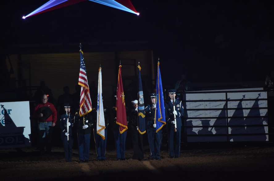 """The Goodfellow Air Force Base Joint-Service Color Guard present the colors during the 85th Annual San Angelo Stock Show and Rodeo Military Appreciation Night at the Foster Communications Coliseum in San Angelo, Texas, Feb. 15, 2017. Goodfellow Air Force Base's Patriotic Blue sang """"The Star-Spangled Banner"""" during the presentation of the colors. (U.S. Air Force photo by Staff Sgt. Laura R. McFarlane/Released)"""
