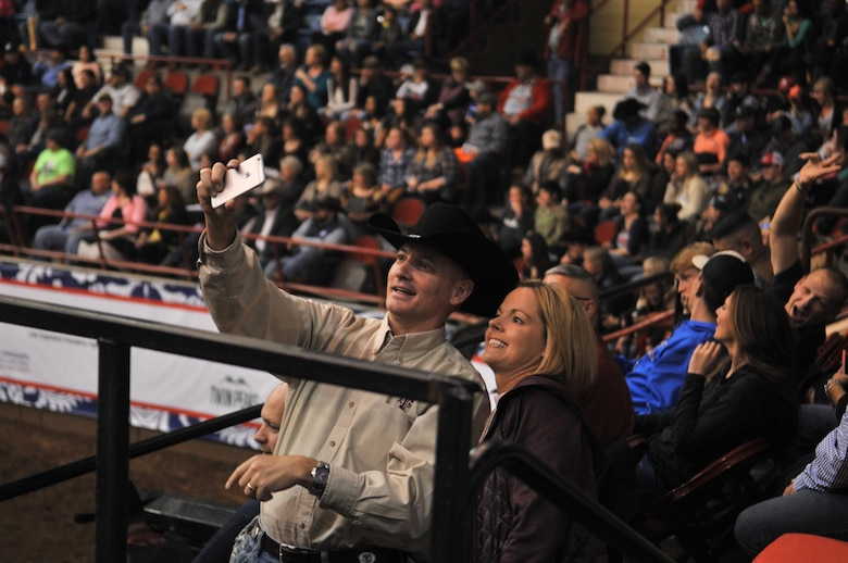 U.S. Air Force Col. Michael Downs, 17th Training Wing Commander, and Chief Master Sgt. Bobbie Riensche, 17th TRW Command Chief, take a selfie before the 85th Annual San Angelo Stock Show and Rodeo Military Appreciation Night at the Foster Communications Coliseum in San Angelo, Texas, Feb. 15, 2017. The rodeo honored military members with special presentations during the night. (U.S. Air Force photo by Staff Sgt. Laura R. McFarlane/Released)