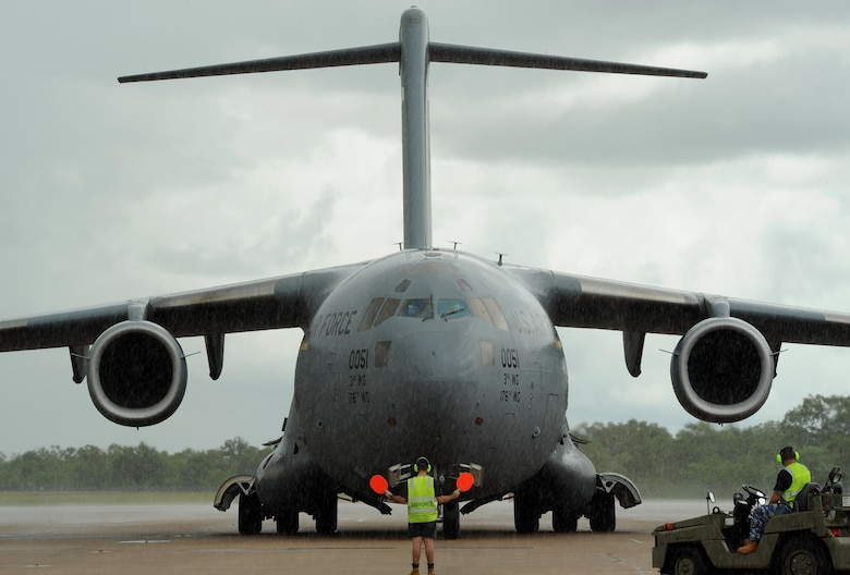 A member of the Royal Australian Air Force marshals a U.S. Air Force C-17 Globemaster, arriving from Joint Base Elmendorf-Richardson, Alaska, on the flightline at Royal Australian Air Force (RAAF) Base Tindal, Feb. 13, 2017. U.S. Airmen arrived via the C-17 to support twelve F-22 Raptors, joining approximately 200 Airmen at RAAF Base Tindal as part of the Enhanced Air Cooperation (EAC) Initiative under the Force Posture Agreement between the U.S. and Australia. EAC creates the foundation for an enhanced rotational presence of U.S. military personnel in Australia to promote interoperability, build upon our already strong alliance, and reaffirm our commitment to the Indo-Asia-Pacific region.  (U.S. Air Force photo/Staff Sgt. Alexander Martinez)