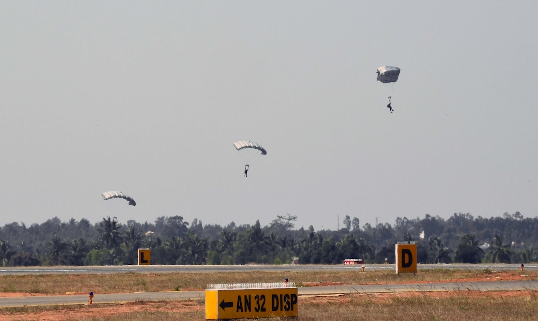 U.S. and India Special Forces paratroopers descend from a U.S. Air Force C-130J Super Hercules following a joint U.S. and India combined free-fall jump during Aero India 2017 at Air Force Station Yelahanka, Bengaluru, India, Feb. 15, 2017. The jump was one of the highlights of the tradeshow that demonstrates the U.S. commitment to the security of the Indo-Asia-Pacific region, promotes the standardization and interoperability of equipment, and displays capabilities critical to the success of current and future military operations. (U.S. Air Force photo by Capt. Mark Lazane)
