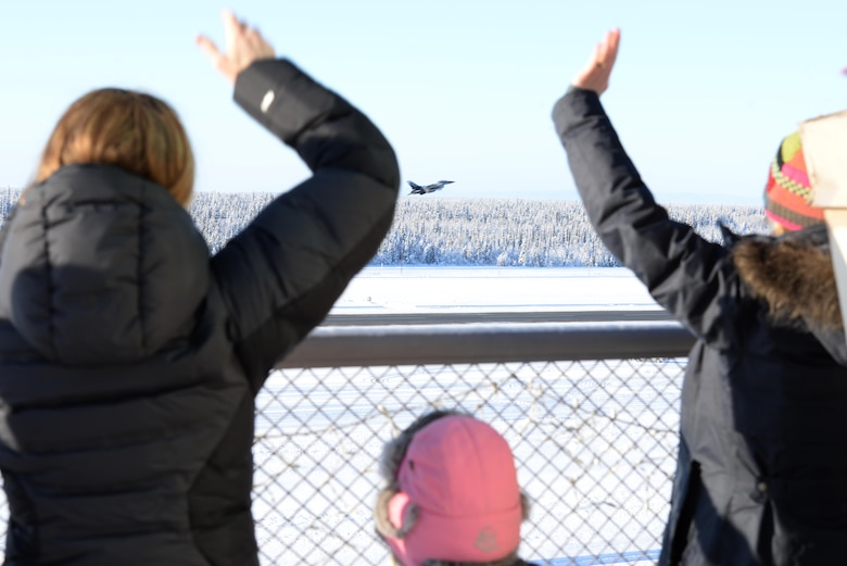 Family members wave goodbye to pilots as they take off Feb. 12, 2017, at Eielson Air Force Base, Alaska. The pilots from he 18th Aggressor Squadron departed to support COPE NORTH 2017, an exercise which provides the opportunity for tri-lateral field training exercises which imnproves combat readiness, develops synergistic humanitarian assistance and/or disaster relief operations, and increases interoperability between the U.S., Royal Australian Air Force and Japanese Air Self-Defense Force. (U.S. Air Force Photo by Airman Eric M. Fisher)