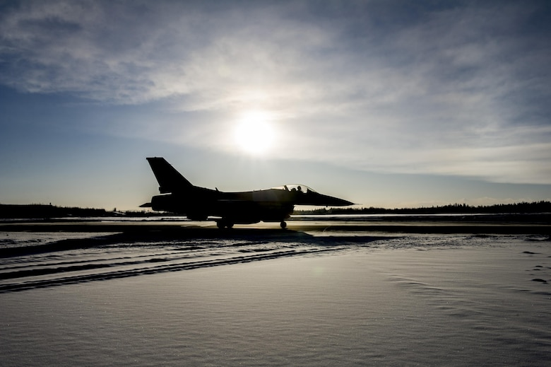 A U.S. Air Force F-16 Fighting Falcon aircraft assigned to the 18th Aggressor Squadron, waits on the taxi-way Feb. 12, 2017, at Eielson Air Force Base, Alaska. The aircraft was part of the group that deployed to Andersen Air Force Base, Guam, in support of COPE NORTH 2017, an exercise designed to increase combat readiness among coalition forces. (U.S. Air Force photo by Airman Isaac Johnson)
