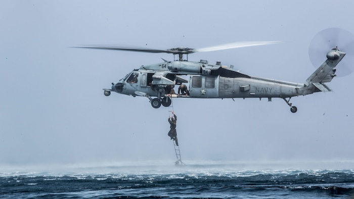A Marine with the Maritime Raid  Force climbs a caving ladder attached to an MH-60 Seahawk during a helocast training evolution near the USS Makin Island (LHD 8) afloat in the Indian Ocean, Nov. 28, 2016. The training consisted of Marines jumping out of CH-53 Super Stallions with a Combat Rubber Raiding Craft, which simulated the MRF team traveling a long distance before being dropped in the ocean to continue their mission using a CRRC. The Marines are with the 11th Marine Expeditionary Unit.