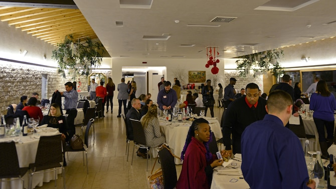 """Couples mingle and find their seats before a """"Forever For Real"""" event in Polcenigo, Italy, Feb. 11, 2017. The event, hosted by the base chapel and Airman and Family Readiness Center, consisted of a five-course meal and an interactive discussion about finances. (U.S. Air Force photo by Senior Airman Cary Smith)"""