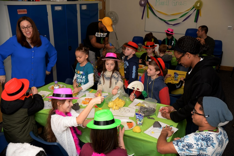 "Volunteers from Team Mildenhall lead activities for the kids during the Hearts Apart event Feb. 16, 2017, on RAF Mildenhall, England. These activities included mask-and necklace-making to go along with the ""Mardi Gras"" theme. (U.S. Air Force photo by Airman 1st Class Tenley Long)"