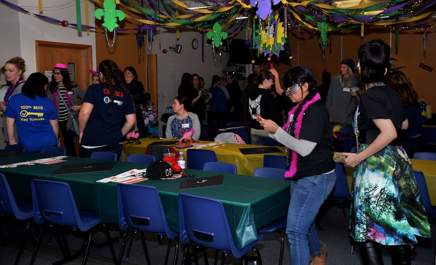 """Members of Team Mildenhall socialize during the Hearts Apart event Feb. 16, 2017, on RAF Mildenhall, England. The Hearts Apart events are held monthly, and this month's theme was """"Mardi Gras,"""" complete with decorations and New Orleans-themed food. (U.S. Air Force photo by Airman 1st Class Tenley Long)"""